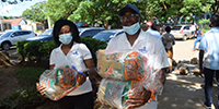 Ndau right and fellow PCL staff member Dalitso Chawuwa carry Christmas parcels for distribution to patients at QECH